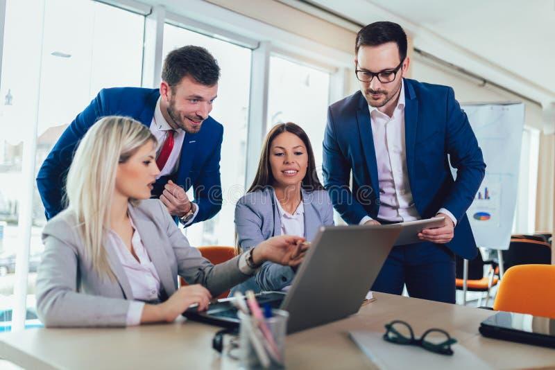 工作和使用膝上型计算机的小组年轻商人,当一起时坐在办公桌 库存照片