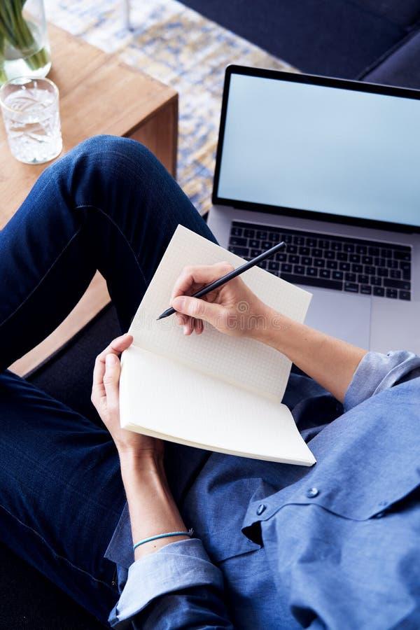 工作和写在纸笔记本的企业家或学生,使用膝上型计算机在舒适的象家一样的大气 关闭手m 库存图片