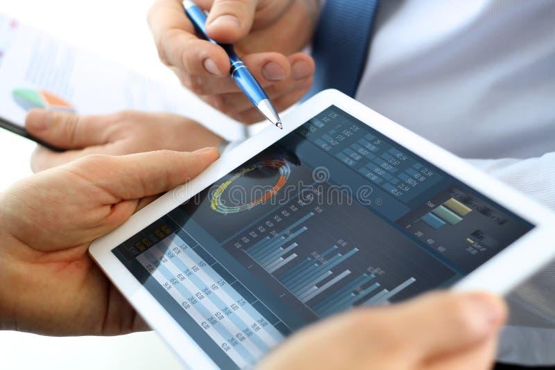 工作和分析在一种数字式片剂的企业同事财政图 库存照片