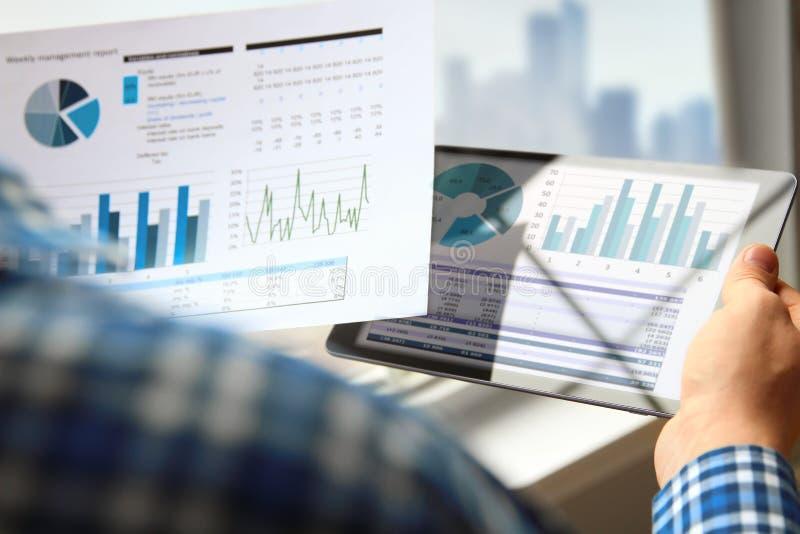 工作和分析在的商人财政图图表使用片剂 免版税图库摄影