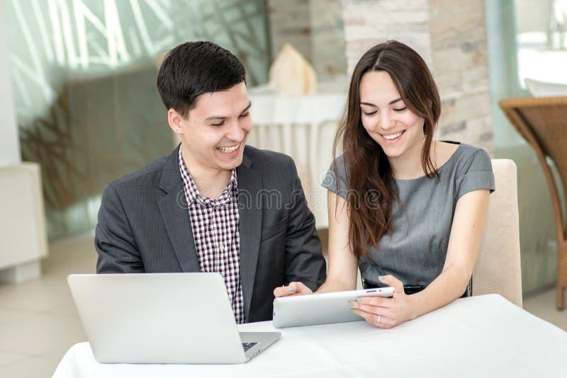 工作和爱 在坐在稀土的一张桌上的爱的年轻夫妇 库存图片