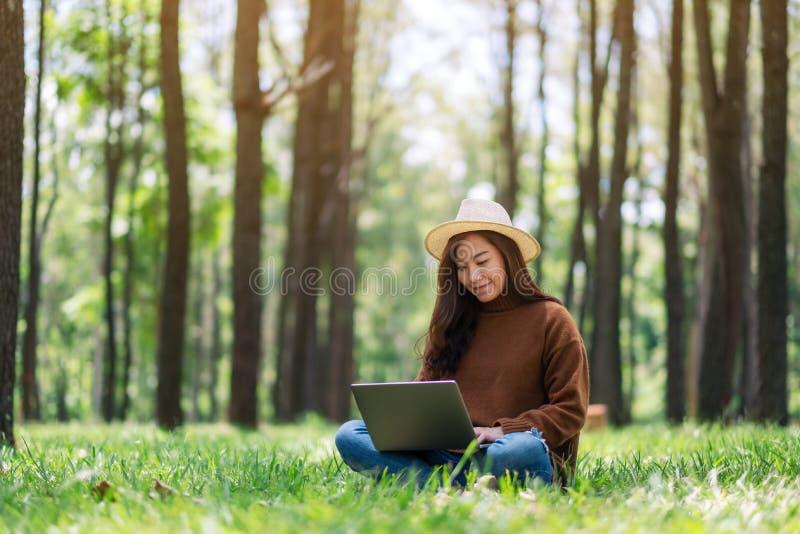 工作和键入在膝上型计算机键盘的妇女,当坐在公园时 免版税库存图片