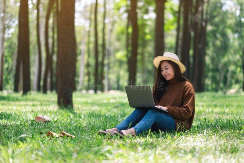 工作和键入在膝上型计算机键盘的妇女,当坐在公园时 库存图片