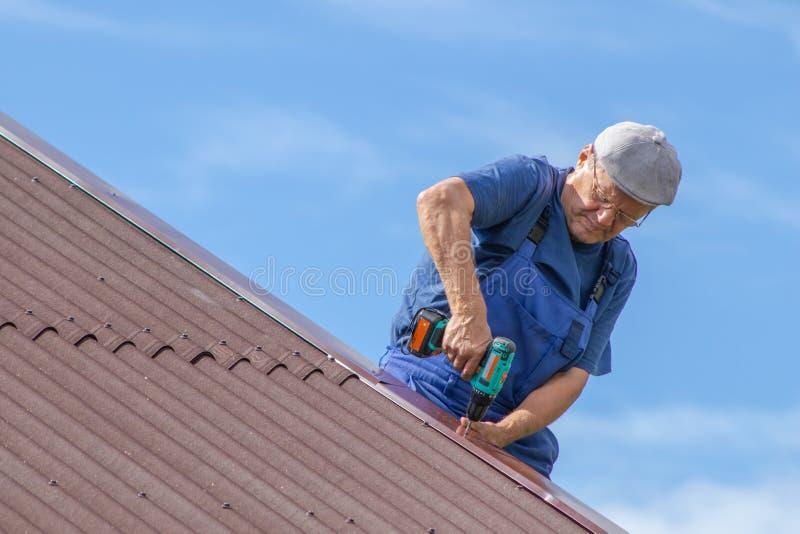 工作在一个房子的屋顶的热的老人有电螺丝刀的,佩带保险装置,工作衣物,蓝色总体, da 免版税库存照片