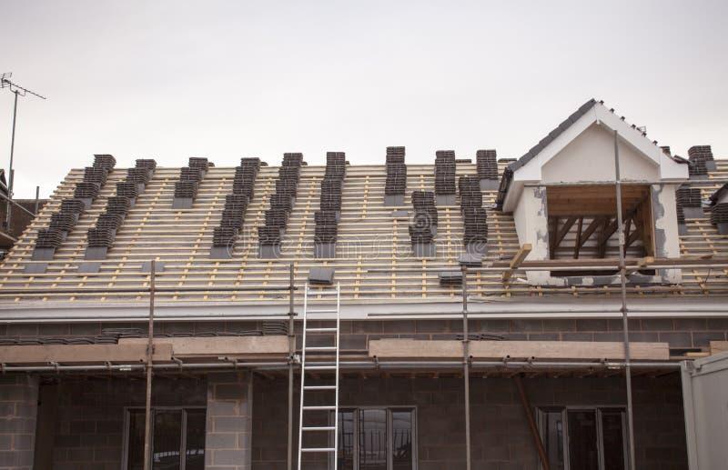 工作在一个新,二层,商业公寓的屋顶覆盖和舷外架或者梯子 库存照片