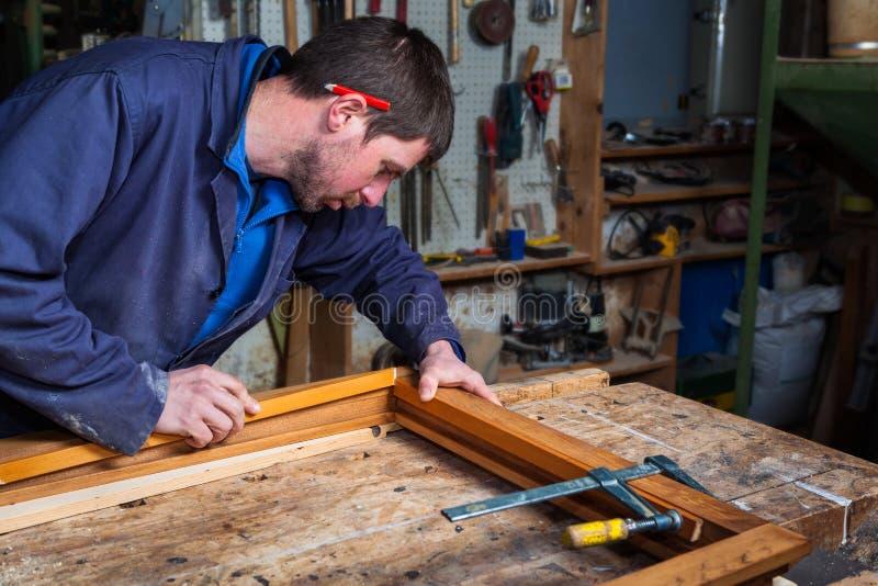 工作在一个木窗架的木匠在他的车间 免版税库存图片