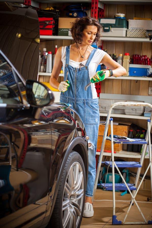 工作在一个汽车修理店的一辆汽车的技工妇女 库存照片