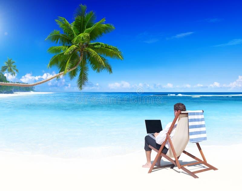 工作在一个热带海滩的商人 免版税库存图片