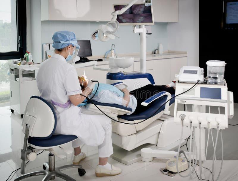工作在一个牙齿诊所的牙医 免版税库存图片