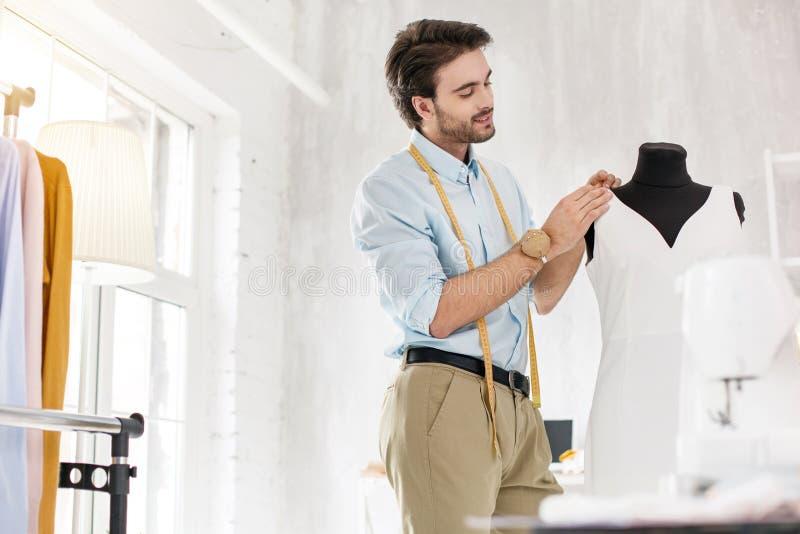 工作在一件新的礼服的严肃的裁缝