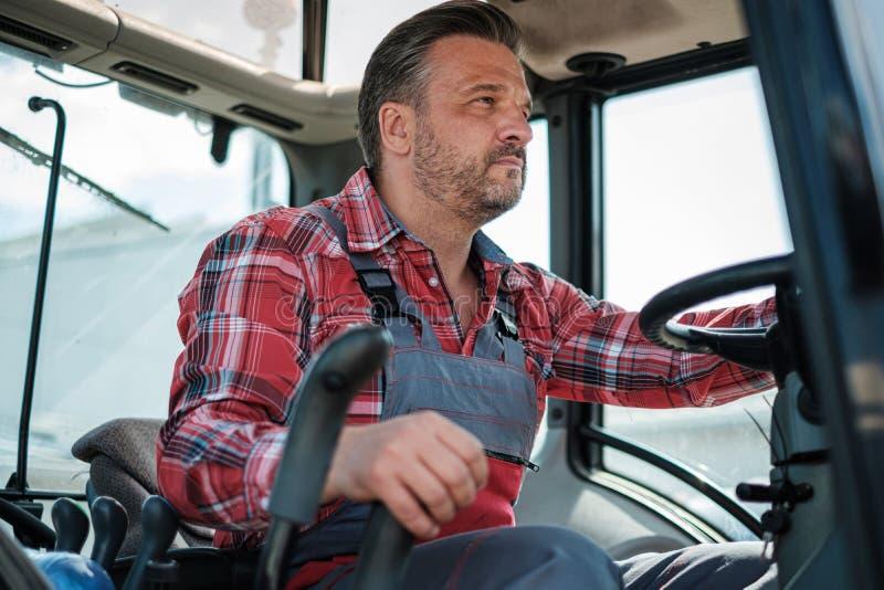 工作在一台现代拖拉机的农夫 免版税库存图片