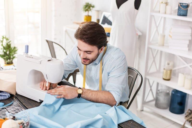 工作在一台缝纫机的微笑的裁缝