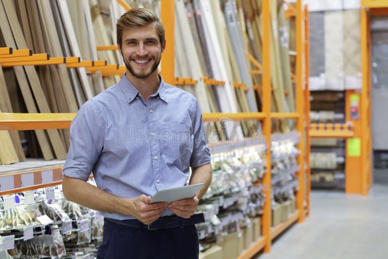 工作在一家付现自运的批发商店的一名微笑的年轻仓库工作者的画象 库存照片
