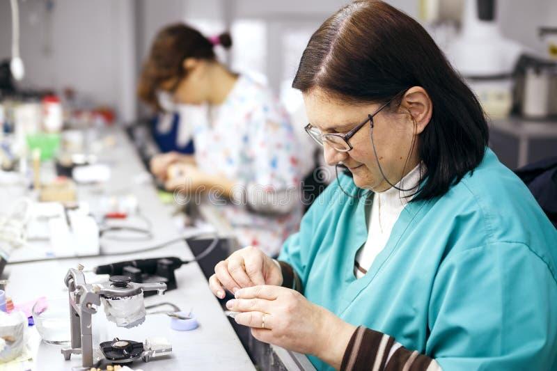工作在一条牙齿假肢的女性牙科技师在牙齿实验室 库存照片