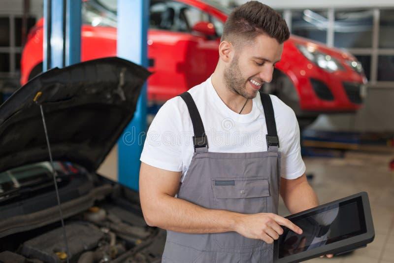 工作在一种数字式片剂的汽车机械师 免版税库存图片