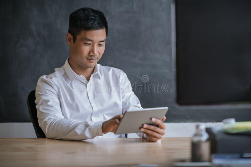 工作在一种片剂的微笑的亚洲商人在办公室 库存图片