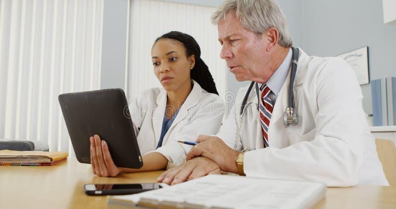 工作在一种片剂的黑人和白种人医生在办公室 图库摄影