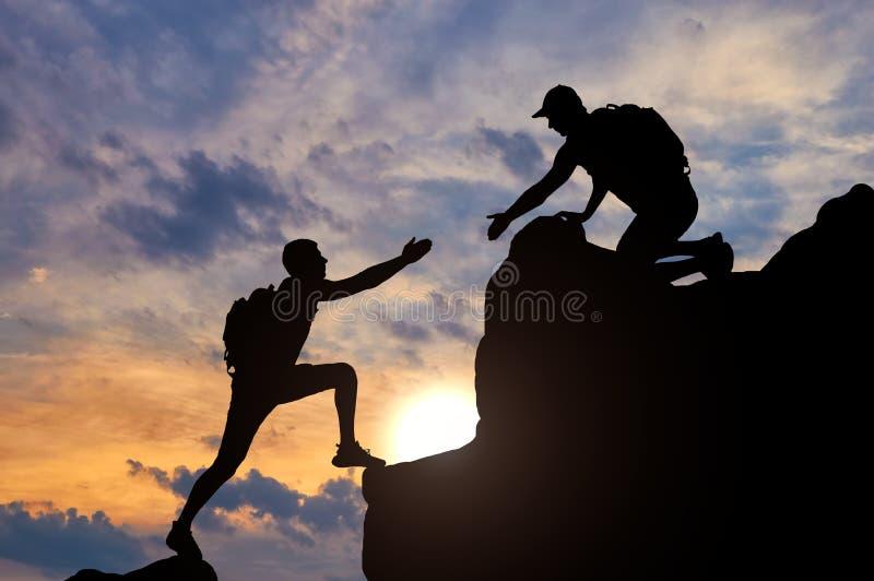 工作在与伙伴的一个队的一名男性登山家的剪影,给他一个帮手 皇族释放例证