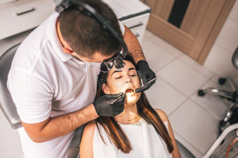 工作在与女性患者的牙齿诊所的牙医柴的 免版税库存照片