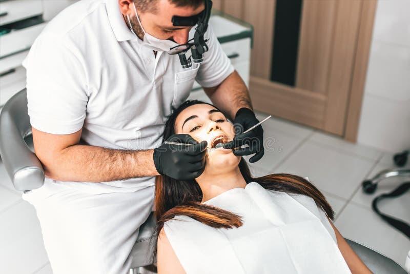 工作在与女性患者的牙齿诊所的牙医柴的 免版税库存图片