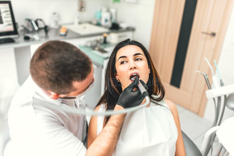 工作在与女性患者的牙齿诊所的牙医柴的 免版税图库摄影