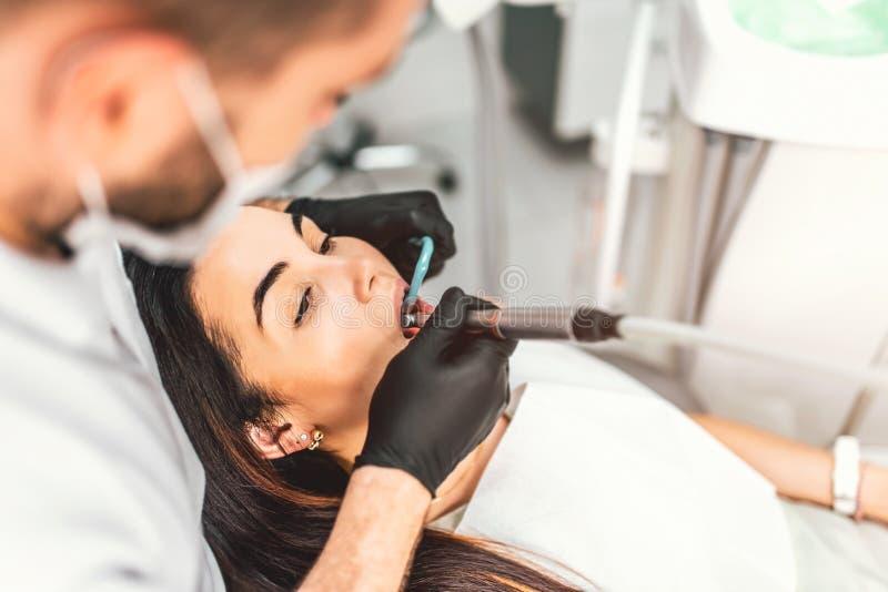 工作在与女性患者的牙齿诊所的牙医柴的 库存图片