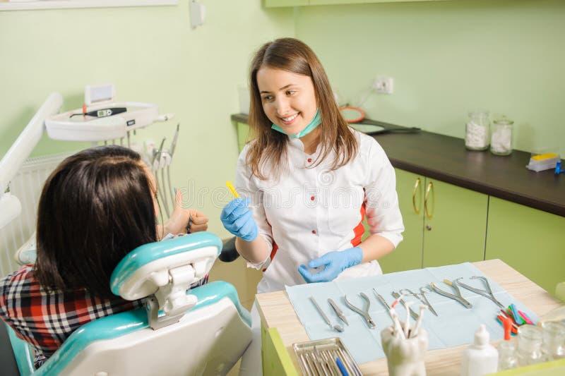 工作在与女性的牙齿诊所的女性牙医patien 库存照片