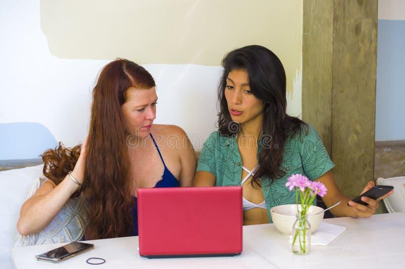 工作在与手提电脑的办公室咖啡馆的年轻愉快和美丽的白种人和西班牙妇女作为数字商务伙伴 免版税图库摄影