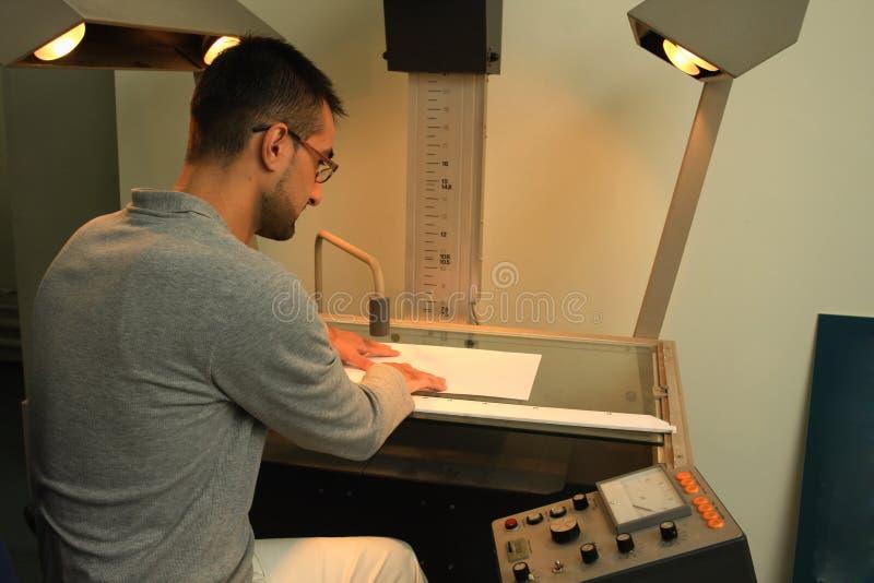 工作在与电子的桌上的人 免版税库存图片
