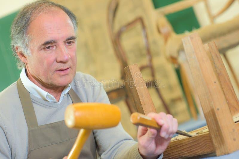 工作在与锤子和凿子的木桌上的木匠 库存照片