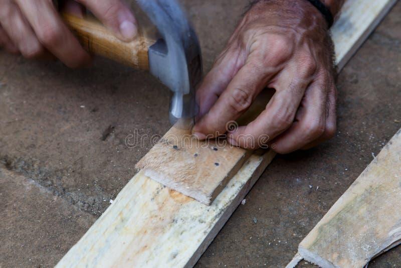 工作在与锤子的木头的人 免版税库存照片