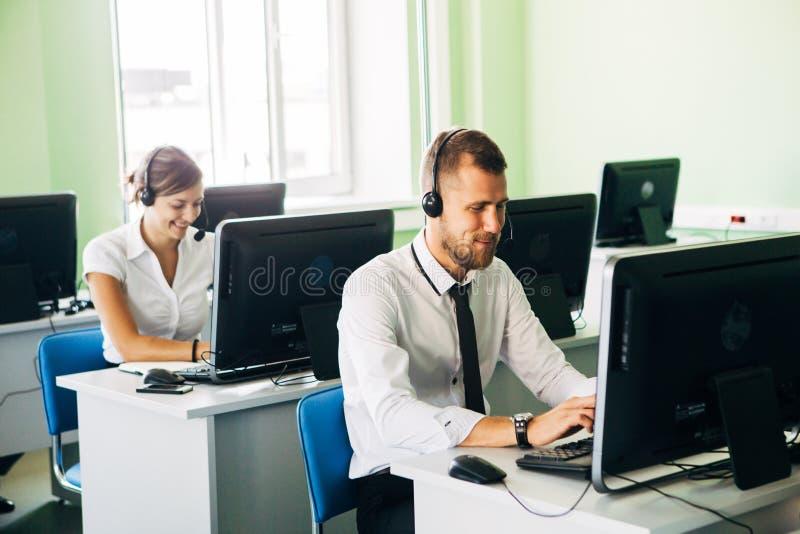 工作在与他的同事的一个电话中心的年轻女实业家 免版税库存照片