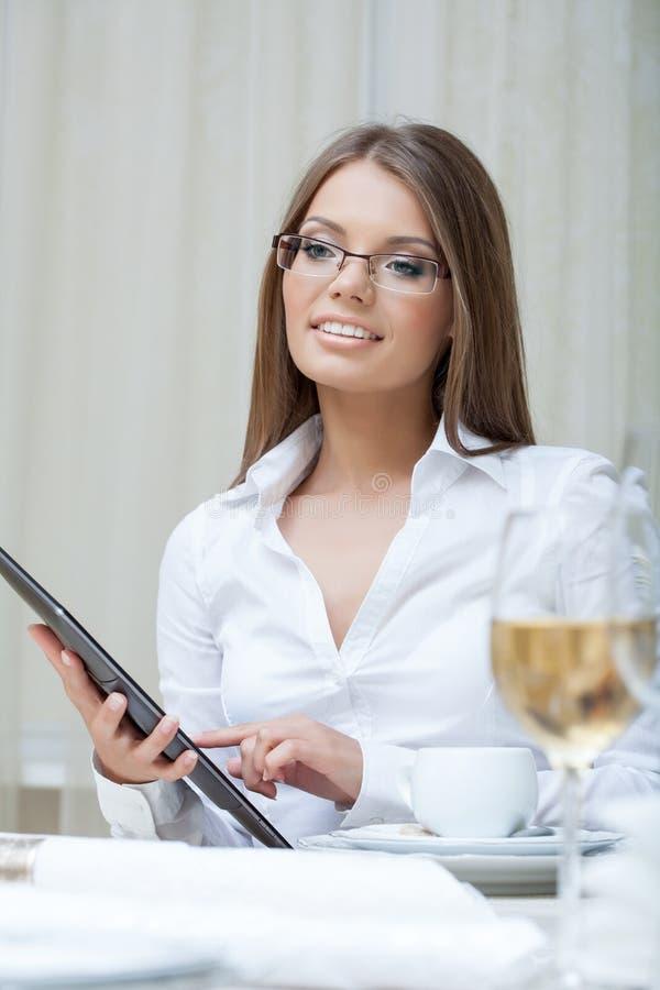 工作在个人计算机片剂的微笑的女商人 免版税图库摄影