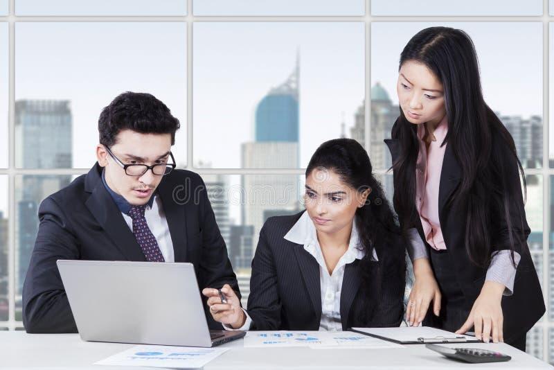 工作在书桌上的三位企业家在办公室 免版税库存照片