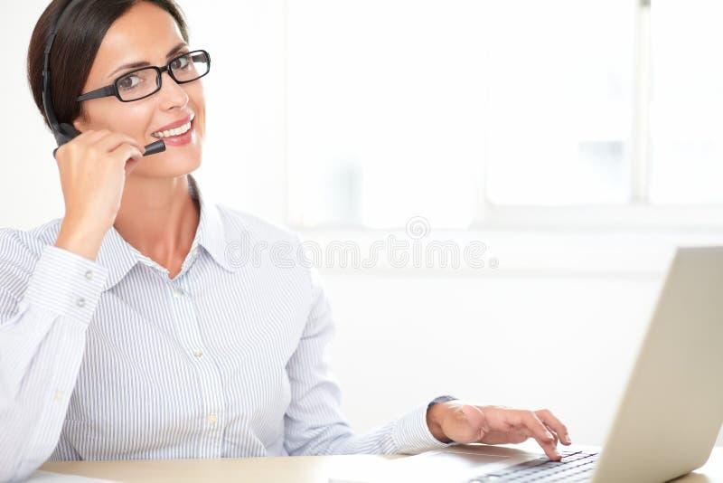 工作在书桌上的迷人的callcenter雇员 库存图片