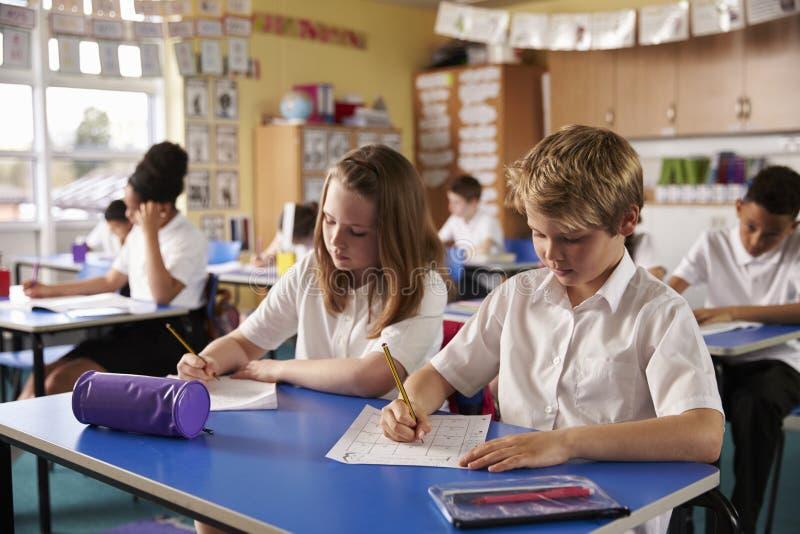 工作在书桌的两个孩子在一间小学教室 免版税图库摄影