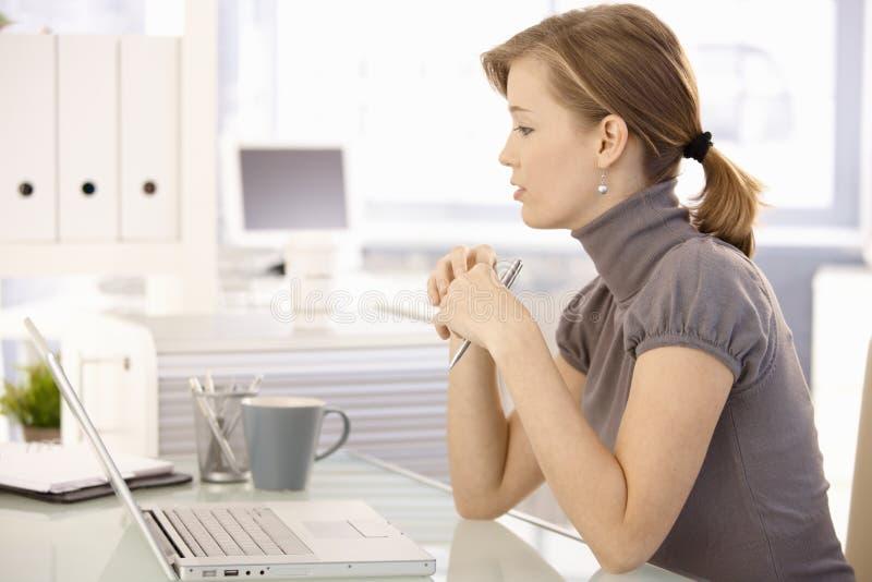 工作在书桌的可爱的女实业家 免版税库存照片