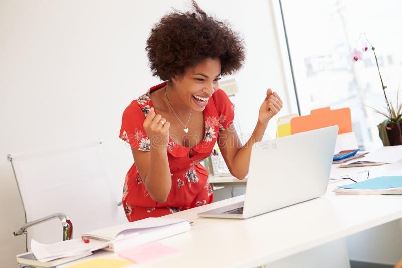 工作在书桌的激动的妇女在设计演播室 库存照片