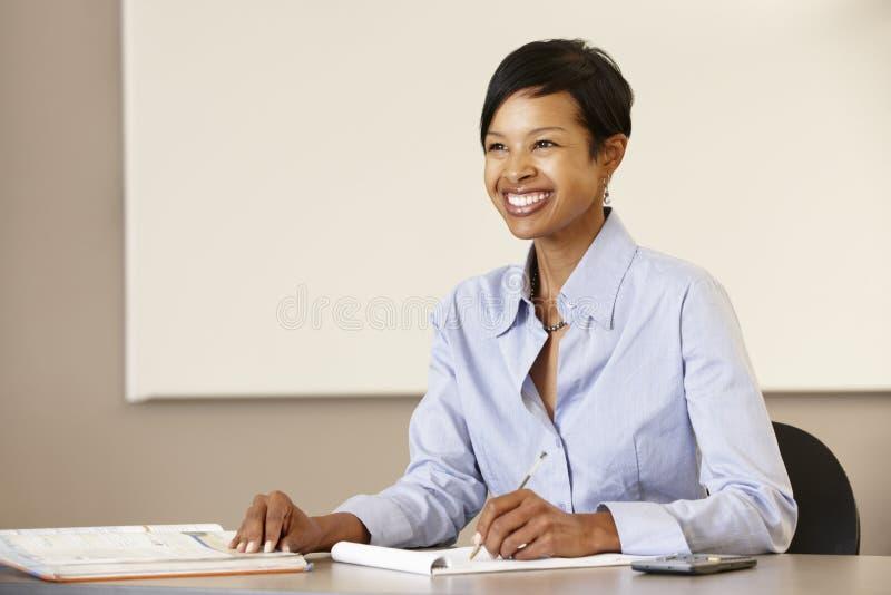 工作在书桌的非裔美国人的老师 库存图片
