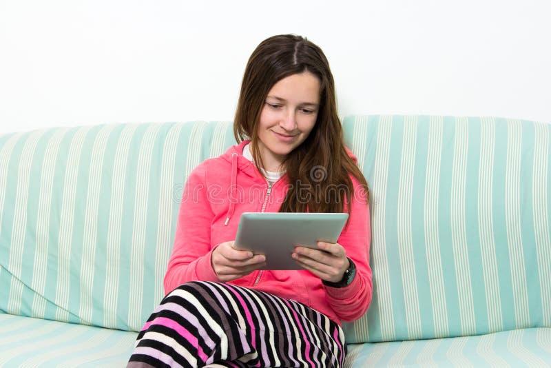 工作在五颜六色的成套装备的表个人计算机的深色的十几岁的女孩 图库摄影