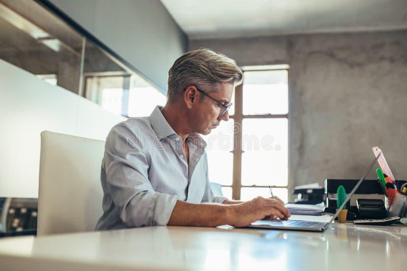 工作在他的书桌的商人 免版税库存照片