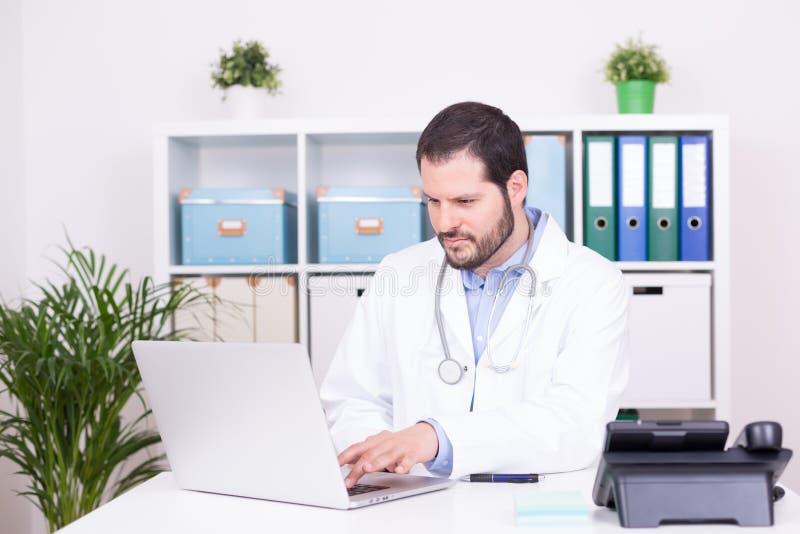 工作在他的办公室的有胡子的医生 事务和医疗概念 库存照片