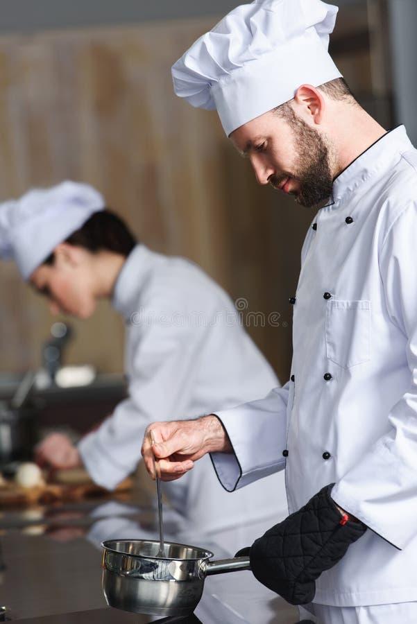 工作在他的女性同事旁边的男性厨师 免版税库存照片