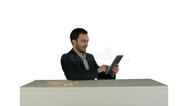 工作在他的桌上的数字式片剂的商人在他的被隔绝的白色背景的办公室 免版税库存照片