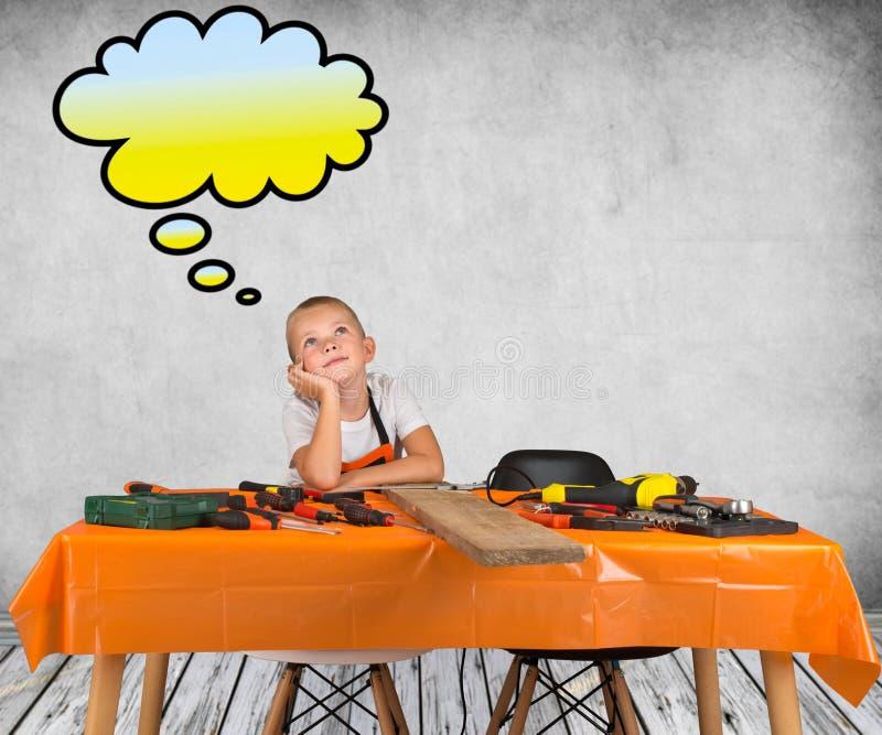 工作在他的父亲` s木匠业车间的男孩 关于什么修造的作梦 免版税图库摄影