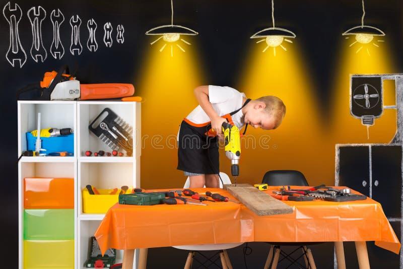 工作在他的父亲` s木匠业车间的男孩 库存图片