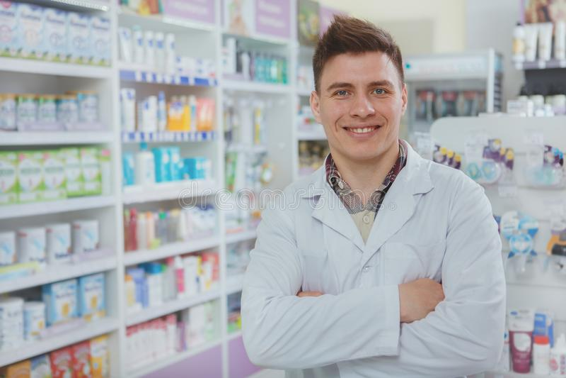 工作在他的药房的英俊的男性药剂师 库存照片