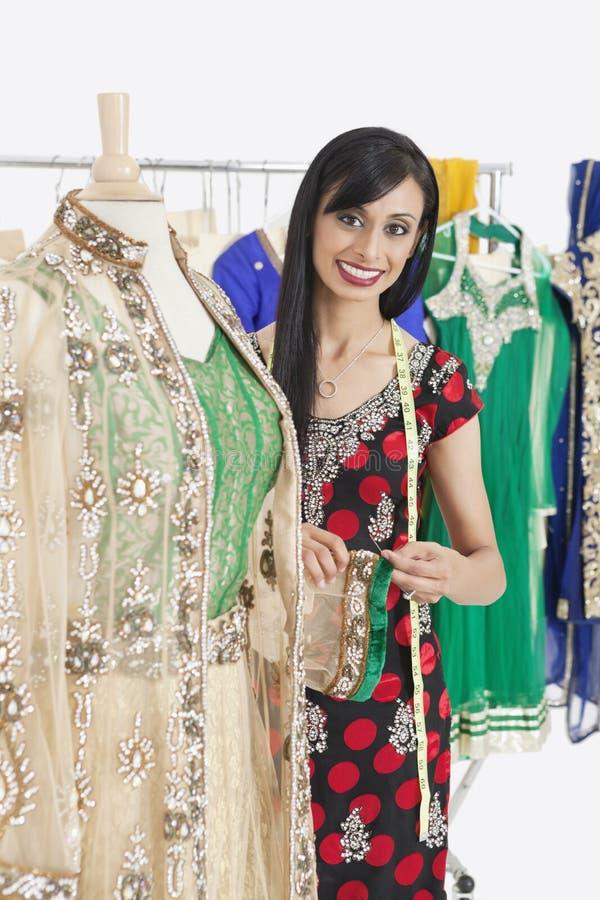工作在传统成套装备的印地安女性裁缝的画象 免版税库存照片