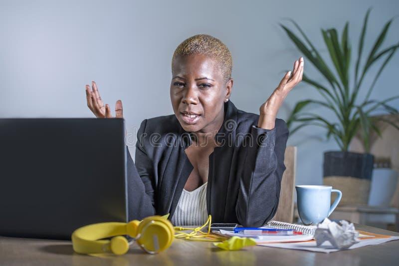 工作在便携式计算机书桌的年轻绝望和被注重的非裔美国人的女商人在办公室感觉sa的痛苦重音 库存图片