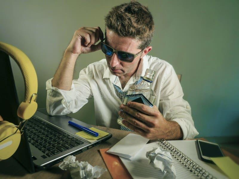 工作在便携式计算机办公桌饮用的酒精伏特加酒瓶的杂乱商人看起来沮丧的和遭受的问题  免版税库存照片